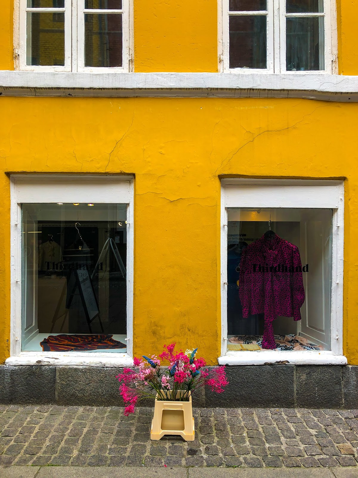 bright yellow building with white window frames in Copenhagen with bunch of pink flowers in centre