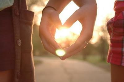 Dos manos femeninas de dos personas distintas formando un corazón en un atardecer.
