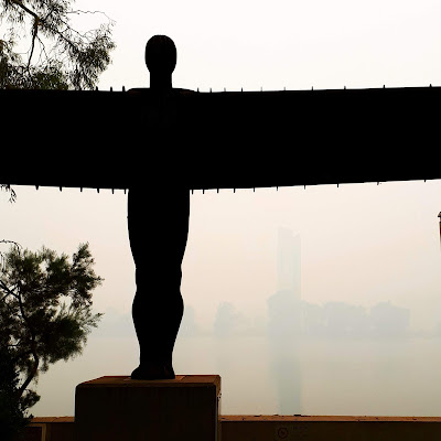 Maquette of the Angel of the North sculpture against a smokey Lake Burley Griffin.