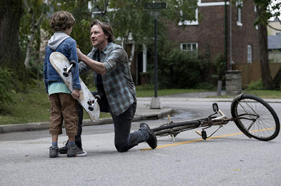 It Chapter Two 2019 movie still where James McAvoy's Bill Denbrough stops a child named Dean (Luke Roessler) in the middle of the street to warn him that Pennywise is after him
