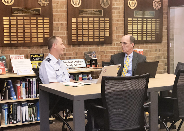 Two men sit at a table in a library