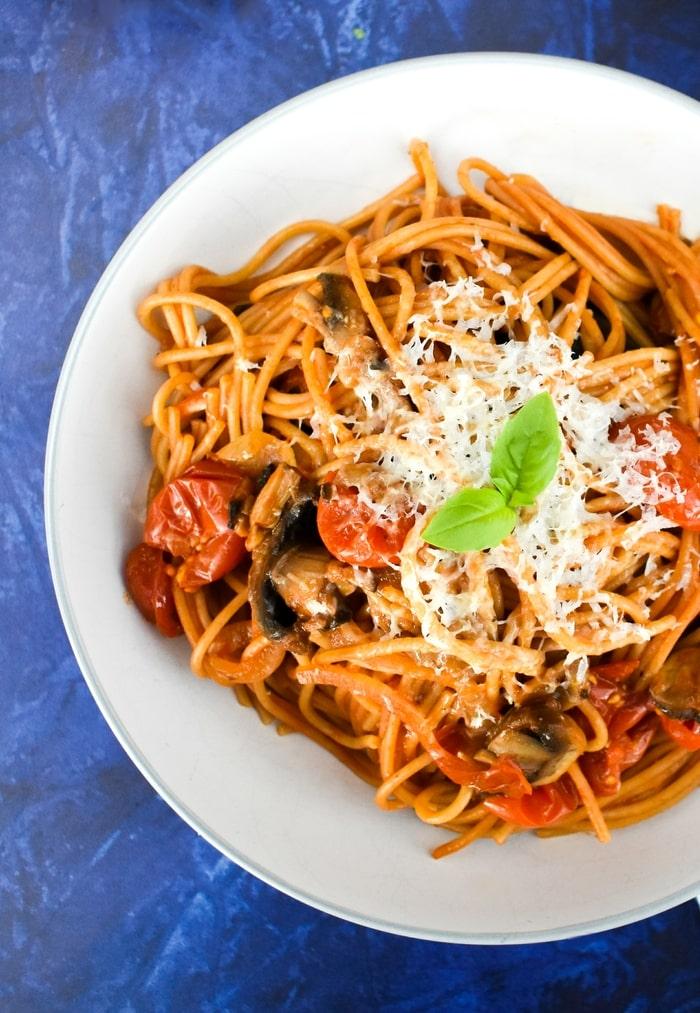 overhead shot of mushroom & tomato spaghetti in a grey pasta bowl