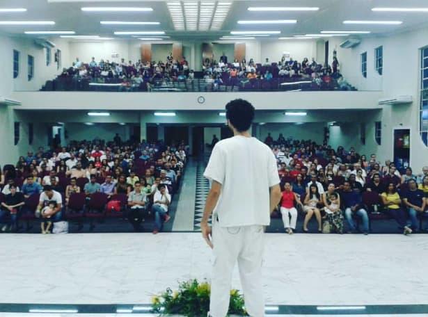 A imagem mostra um jovem artista se apresentando para uma platéia de igreja lotada.