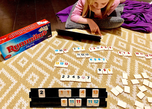 Rummikub has lots more tiles and bigger racks than rubbikub junior, this image is of me playing it with my eldest daughter on the floor