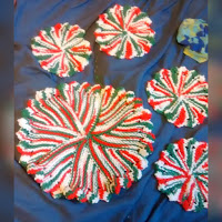 Mixed red, white, and green coaster and trivet with flower petal edges knit in garter stitch