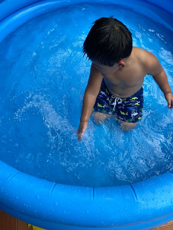 Little boy loving the water in an inflatable kiddie pool