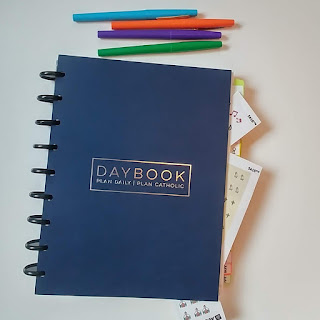 Blue planner with different color markers above it and stickers sticking out of the planner