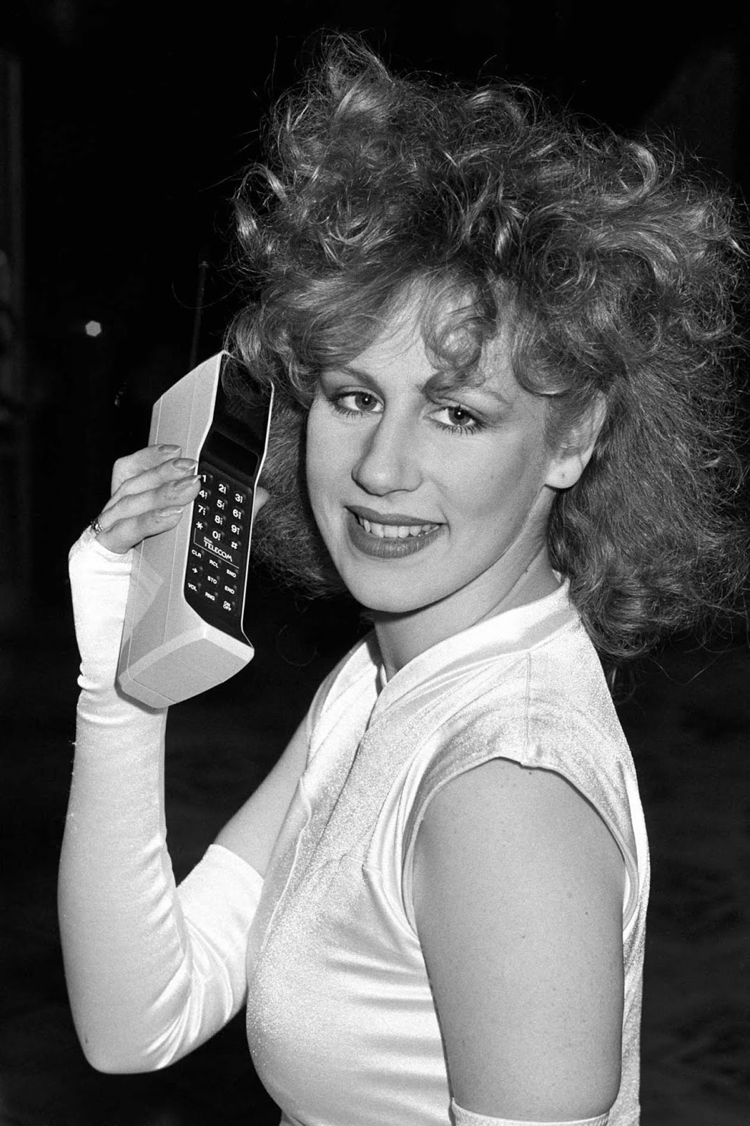 Um modelo posa com um telefone no lançamento do serviço de celular do sistema de rádio celular Cellnet em Londres. 1985.