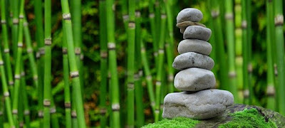 An image of a green garden with bamboo sticks in the back and a tower of rocks in the front.