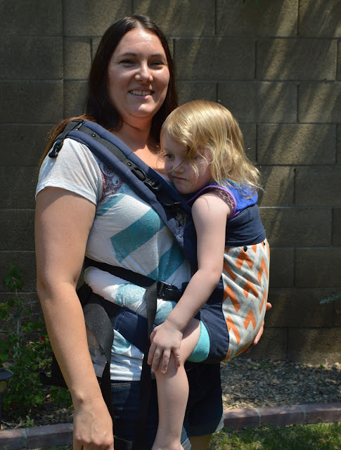 White woman with long dark hair wears white, blond haired toddler in a orange and white chevron print soft structured carrier.  Baby is worn on her hip.