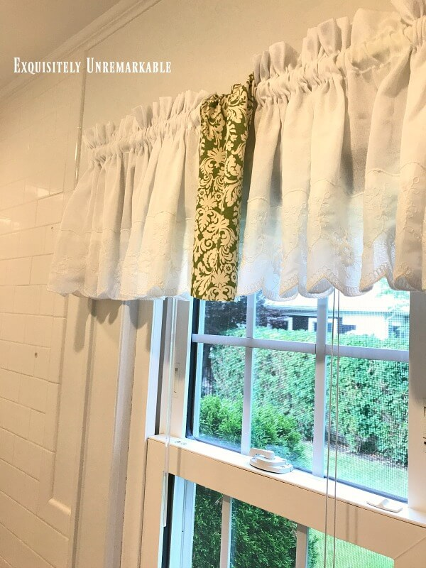 White curtain with a strip of green fabric hanging in middle on bathroom window