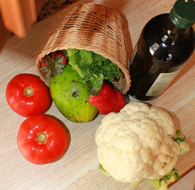This is a basket full of fresh vegetables and an olive oil bottle is in the photo