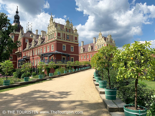 A beige sand paved path lined by lemon trees planted in green pots, that leads to a reddish painted renaissance castle.