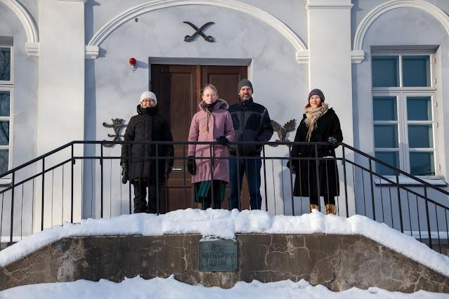 Neljä ihmistä rakennuksen sisäänkäynnin edessä.