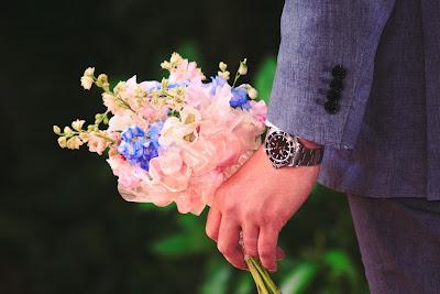 男性が左手に花束を持っている