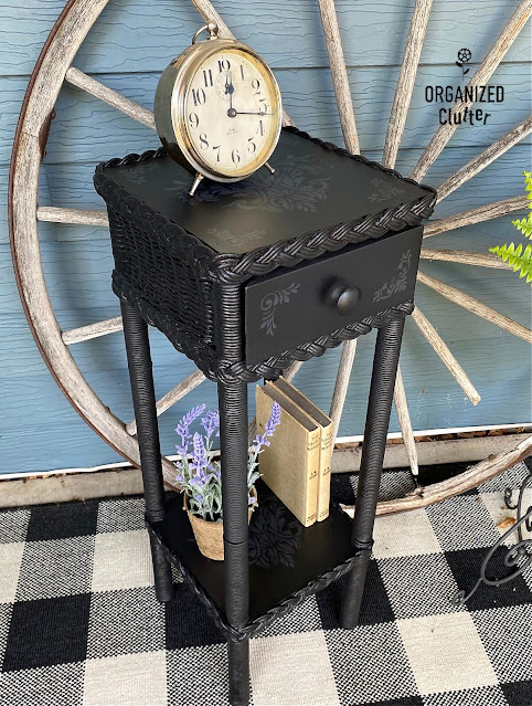 Photo of a black painted plant stand/table with monochromatic stenciling