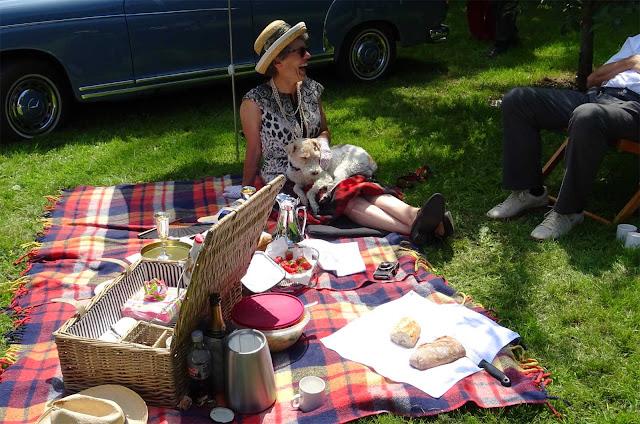 karierte Picknick Decke mit Korb und Frau mit Hund auf den Beinen auf Schloss Merode