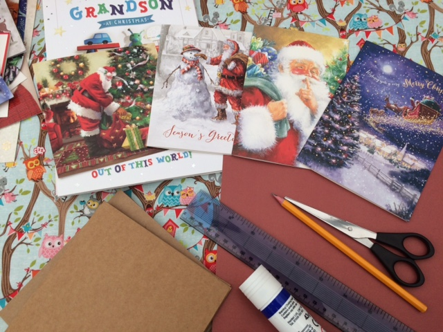 Pile of Christmas cards with glue, ruler, pencil, scissors, a pile of card and a pack of plain cards