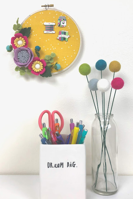 enamel pins stored in embroidery hoop wreath embellished with felt flowers