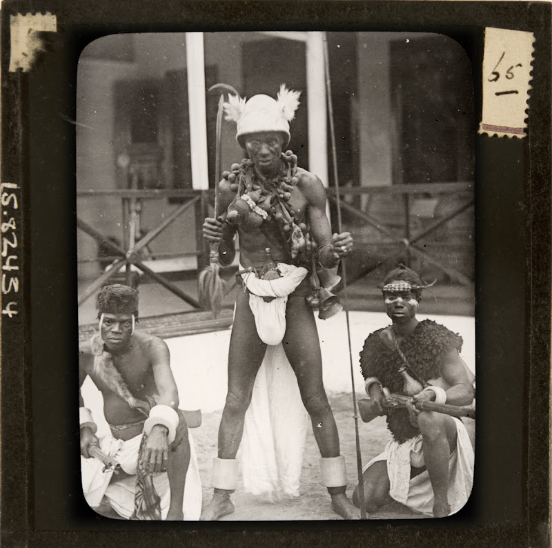 Photo of three Igbo men in loin cloths posing for the camera. Then man in the middle is elderly and standing with a knife raised, two men squat flanking him holding guns.