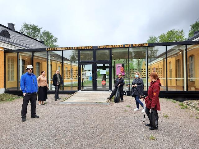 Kuusi henkilöä seisoo taidemuseon edustalla.