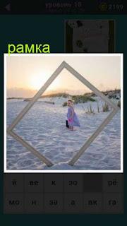 на пляже в песке стоит большая рамка сквозь которую видно девочку