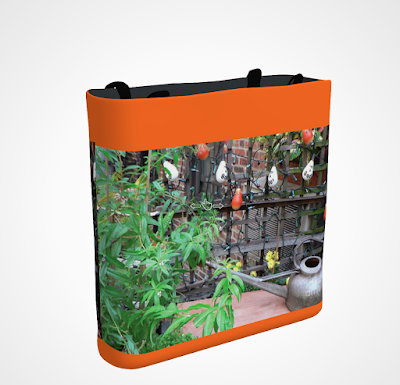 "This screen-shot features an orange tote/bag/pouch which has an image imprinted on it. The picture was taken in my garden when decorated for Halloween. It shows Halloween-themed outdoor lights hanging on a wooden trellis. The tote/bag/pouch is available in three sizes (13"" by 13"", 16"" by 16"" and 18"" by 18"") and can be purchased via Fine Art America@ https://fineartamerica.com/featured/halloween-in-the-garden-patricia-youngquist.html?product=tote-bag  TITLE TEXT: My ""Halloween in the Garden"" tote/bag/pouch is available for purchase via Fine Art America @ https://fineartamerica.com/featured/halloween-in-the-garden-patricia-youngquist.html?product=tote-bag"