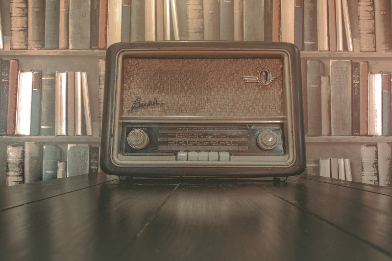 Photo of an old radio sitting on a wooden table in front of a shelf of old books | Lydia Sanders #TwistyMustacheReviews