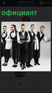 Несколько официантов с подносами готовы к работе. на подносах стоят фужеры и в руках полотенце