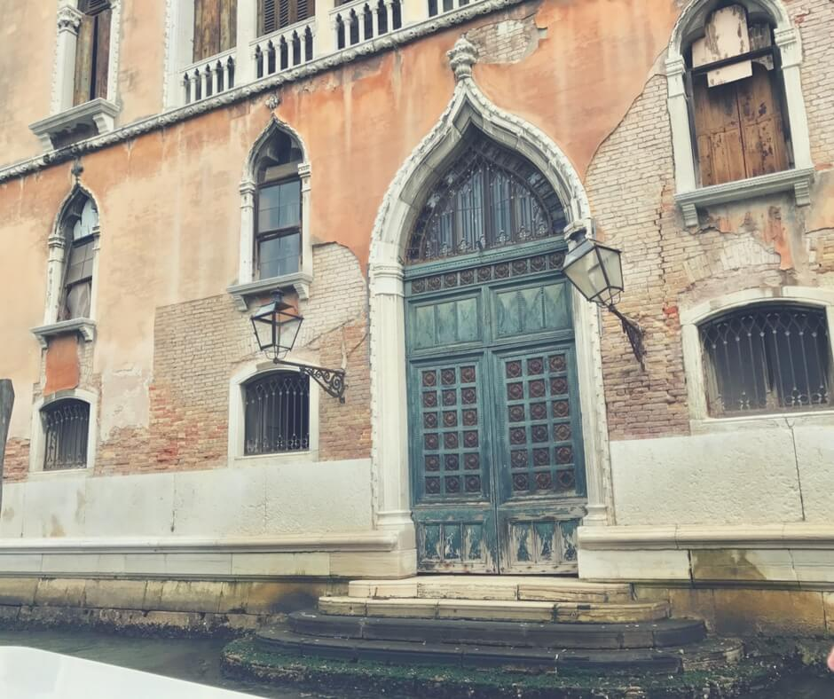 Fancy door leading to steps down to the canal in Venice.