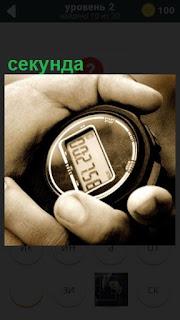 в руках находится секундомер и показывает секунды на циферблате