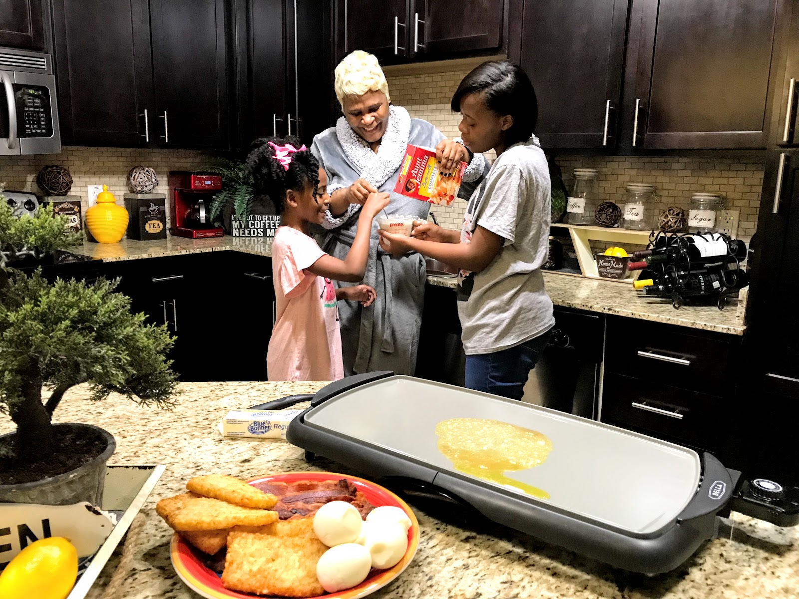 Image: Tangie Bell and daughters cooking pancakes in the kitchen before the first day of school. Seen first on Bits and Babbles blog
