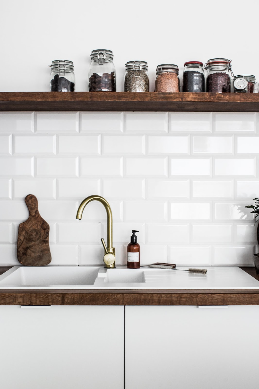 white scandinavian interior, gold kitchen tap, rustic cutting board
