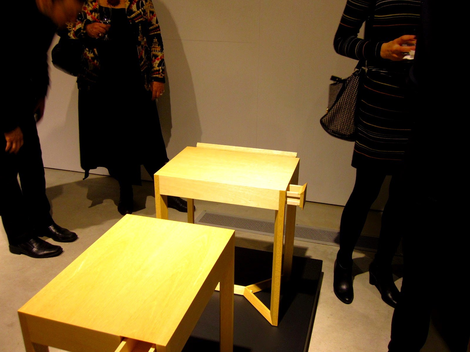 People at an exhibition opening, looking at two small wooden side tables.