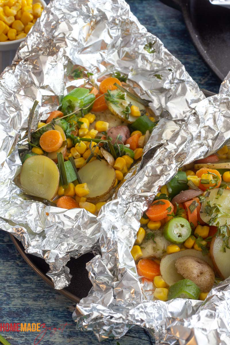 Foil packet showing baked tilapia with corn, okra, potatoes