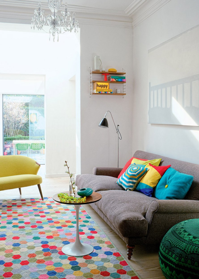 A white and bright living room with lots of colors.