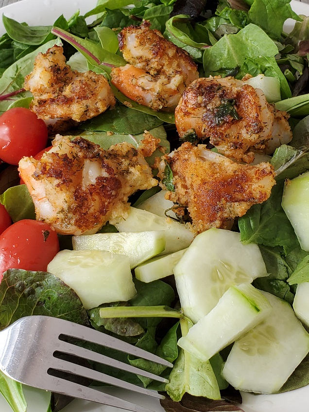 tequila shrimp on top of salad