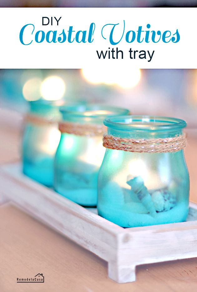 blue coastal votives with jute rope and sand and sea shells on tray