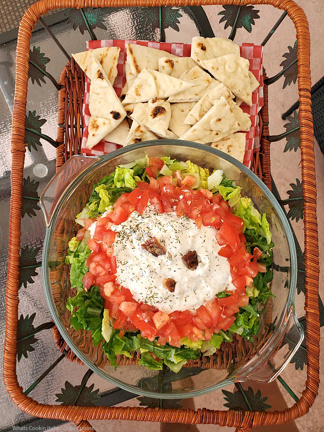 this is a creamy dip with crispy bacon and sour cream tomato and lettuce called BLT dip with pita bread on the side in a palm tree wicker serving tray