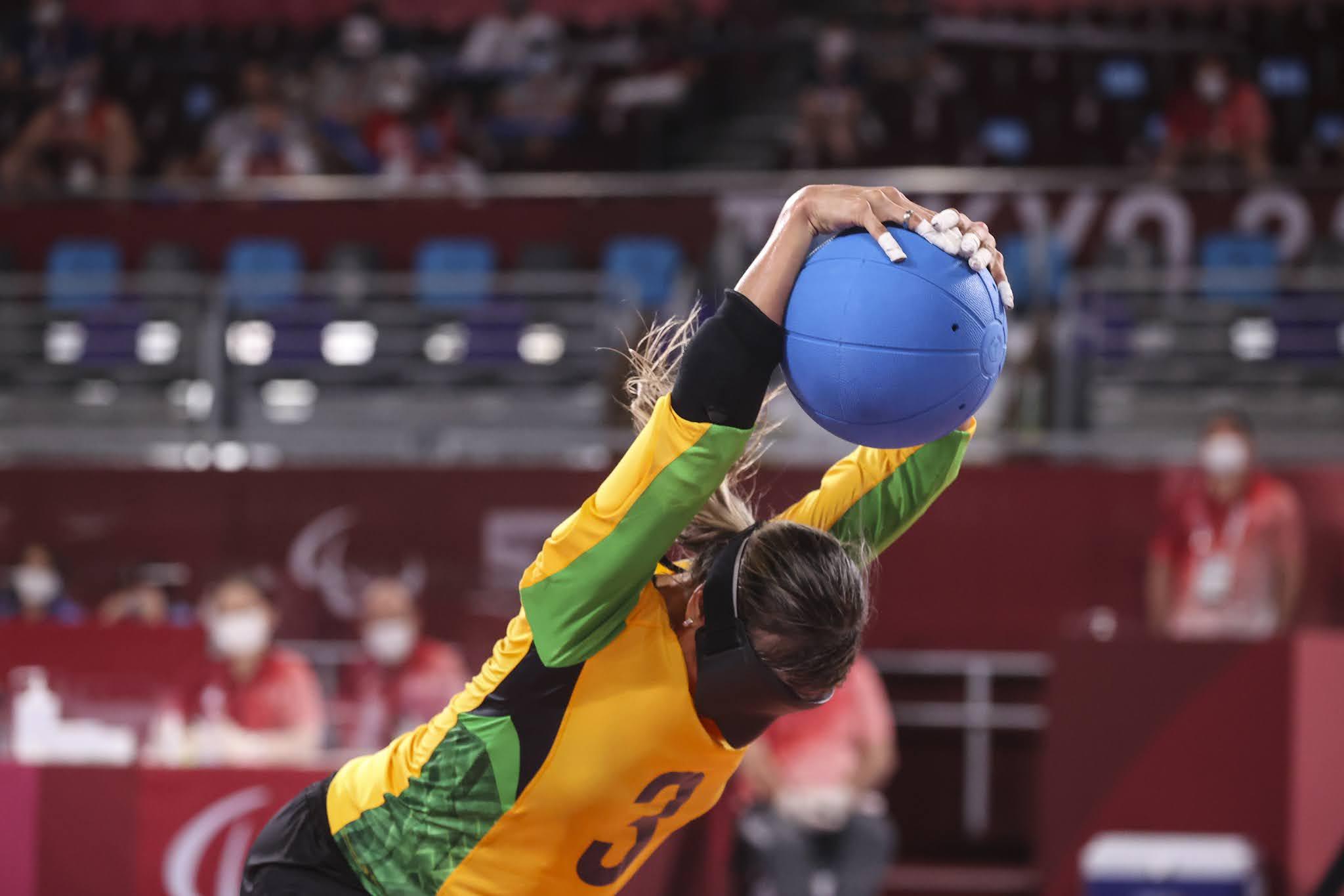 Ana Carolina com a bola azul, virada de costas pronta para arremessar