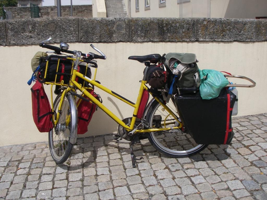 Bicicleta amarela, sobre uma calçada de pedras, encostada na parede e cheia de bagagem do viajante: ilustra a seção a respeito dos textos das linhas de ''Lü / O Viajante'', um dos 64 hexagramas do I Ching, o Livro das Mutações