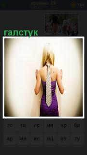 стоит девушка спиной, на которой вист галстук