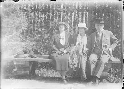 drei von vier Personen auf einer Bank - um 1920