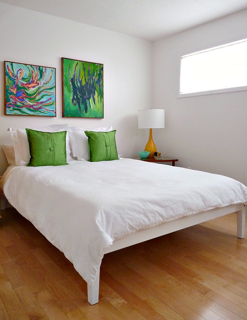 White guest bed with bright artwork