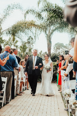 bride and brides father walk down aisle