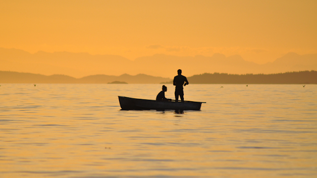 a couple on a rowboat at sunset