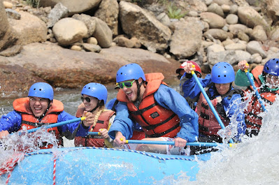 Exterior rafting photo with 7 rafters paddeling in the river.
