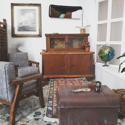 1/12 scale modern miniature lounge scene with two mid-century modern armchairs in grey with dark stained arms and legs, an early twentieth century cupboard, a battered sea chest and afghan rug on the floor. On the wall is a framed picutre of a boat and an abstract landscape. On the windowsill is a globe.