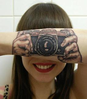 Tatuaje cámara de fotografía en antebrazo