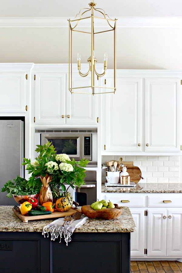 gold lantern pendant, white kitchen cabinets, black kitchen island